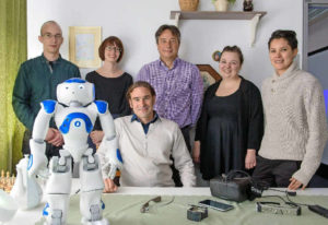 Group picture with NAO robot: Project lead Daniel Sonntag (seated) and some members of his team at DFKI. Photo: Oliver Dietze